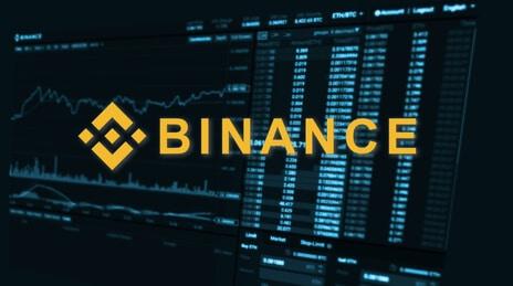 Binance Logo mit Börse im Hintergrund